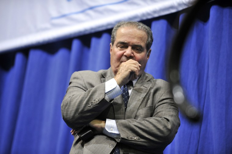 Supreme Court Justice Antonin Scalia stands at the edge of the stage after a question and answer session on Oct. 2, 2013, in Medford, Mass. (Photo by Josh Reynolds/AP)