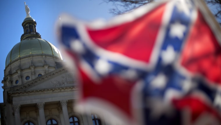 The dome of the State Capitol is seen as a protestor waves a Confederate flag during the March For Life anti-abortion rally, Jan. 22, 2014, in Atlanta, Ga. (Photo by David Goldman/AP)