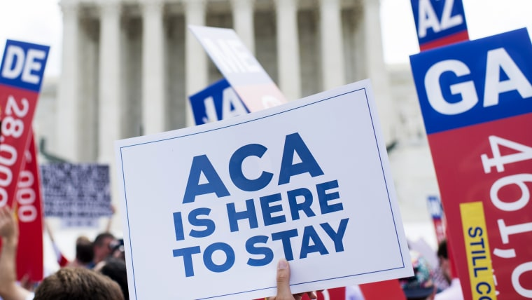 Affordable Care Act supporters wave signs outside the Supreme Court after the court upheld court's Obamacare, June 25, 2015. (Photo By Bill Clark/CQ Roll Call/AP)