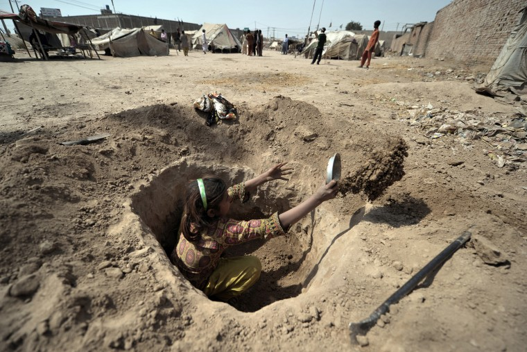 A Pakistani child digs a hole to be used as a toilet for her family at a slum in Multan on March 13, 2012. (Photo by Bay Ismoyo/AFP/Getty)