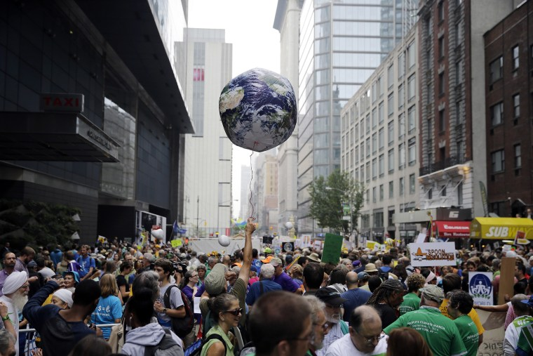 A man holds an earth balloon into the air as people fill the street before a global warming march in New York Sunday, Sept. 21, 2014. (Photo by Mel Evans/AP)