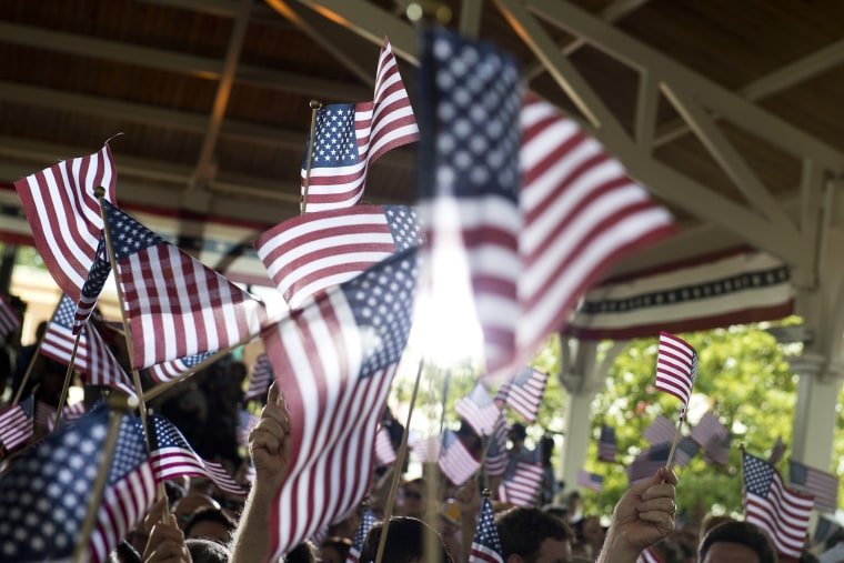People wave American flags at an event. (Photo by Saul Loeb/AFP/Getty)