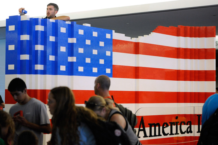 LEGO master builder Chris Steininger places a brick while building the world's largest LEGO American flag to celebrate the opening of the Innovation Wing at the National Museum of American History (Photo by Steve Ruark/AP).