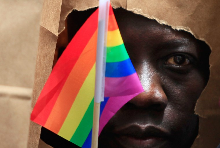 An asylum seeker from Uganda covers his face with a paper bag in order to protect his identity as he marches with the LGBT Asylum Support Task Force during the Gay Pride Parade in Boston, Mass., June 8, 2013. (Photo by Jessica Rinaldi/Reuters)