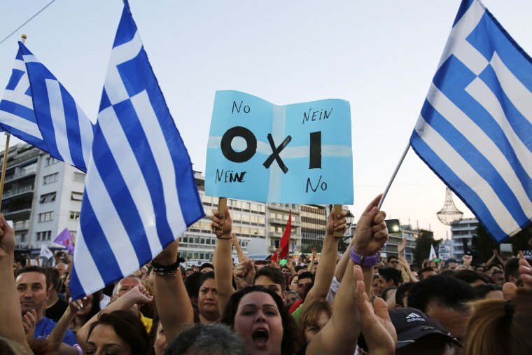 A demonstrator holds a placard reading in Greek, German and English the word ''NO'' during a rally organized by supporters of the No vote in Athens on July 3, 2015. (Photo by Petros Karadjias/AP)