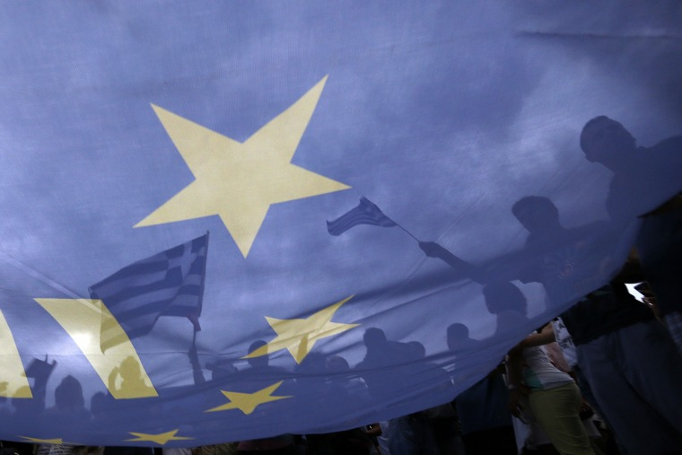 Pro-Euro protestors hold European Union flags during a pro-Euro rally in front of the parliament building in Athens, Greece on Jun. 30, 2015. (Photo by Yannis Behrakis/Reuters)