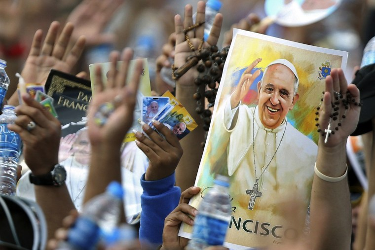 Pilgrims hold up their hands to be blessed by Pope Francis during a Mass at the Samanes Park in Guayaquil, Ecuador on July 6, 2015. (Photo by Fernando Vergara/AP)