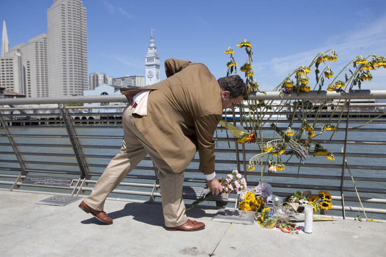 A mourner lays down flowers following a vigil for Kathryn Steinle, Monday, July 6, 2015, on Pier 14 in San Francisco.