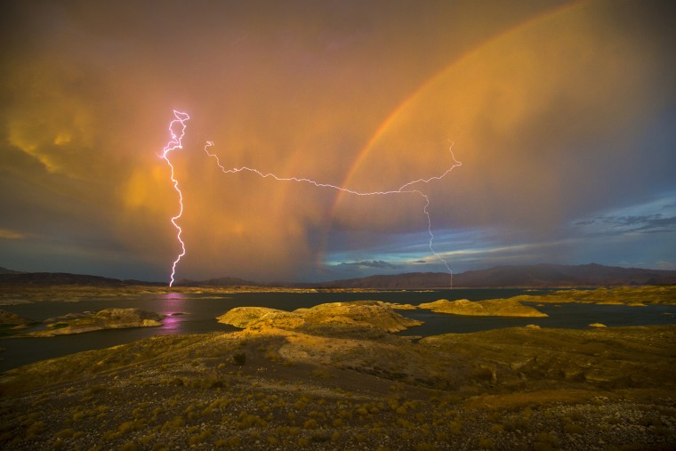Lightning strikes near a rainbow over Lake Mead National Recreation Area in Lake Mead, Nev. on Jul. 1, 2015 (Photo by Allen J. Schaben/Los Angeles Times/Getty).