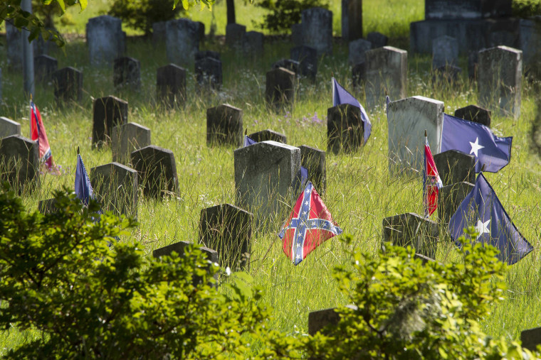 Confederate flags stand next to the headstone's of Confederate States of America (CSA) soldiers at the Magnolia Cemetery in Charleston, S.C., June 26, 2015. (Photo by Jim Watson/AFP/Getty)