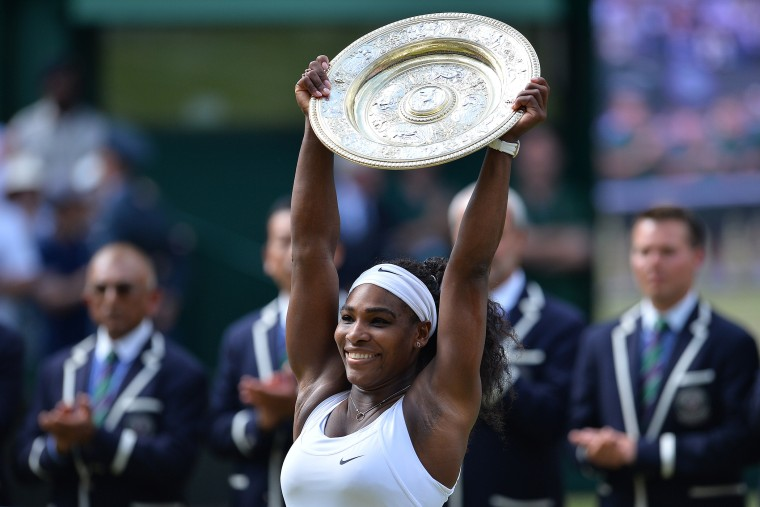 US player Serena Williams celebrates with the winner's trophy, the Venus Rosewater Dish, after her women's singles final victory over Spain's Garbine Muguruza during the 2015 Wimbledon Championships on July 11, 2015. (Photo by Glyn Kirk/AFP/Getty)