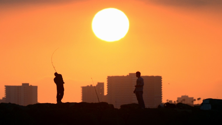 A fisherman casts his line from the rocks at Seal Beach, Calif., as the sun prepares to set on June 28, 2014. (Photo by Frederic J. Brown/AFP/Getty)