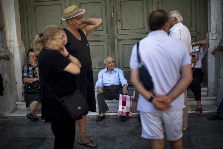 Pensioners sit at the main gate of the national bank of Greece as they wait to withdraw a maximum of 120 euros ($134) for the week in central Athens, July 13, 2015. (Photo by Emilio Morenatti/AP)