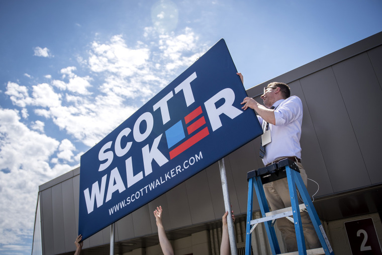 Campaign staff members for Scott Walker, governor of Wisconsin, install a sign in front of the Waukesha County Expo Center in Waukesha, Wis. on July 13, 2015. (Photo by Christopher Dilts/Bloomberg/Getty)