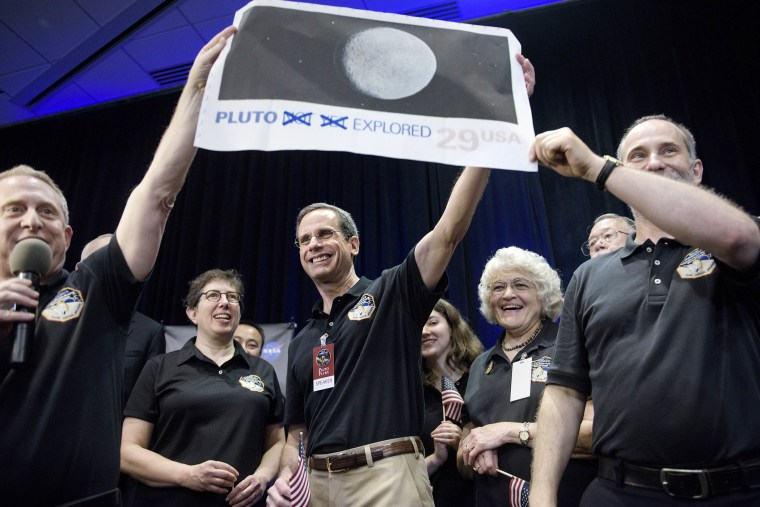 Dr. Allan Stern and others hold up their suggestion for a modified US Post Office stamp of Pluto at the Johns Hopkins University Applied Physics Laboratory on July 14, 2015 in Laurel, Md. (Photo by Brendan Smialowski/AFP/Getty)