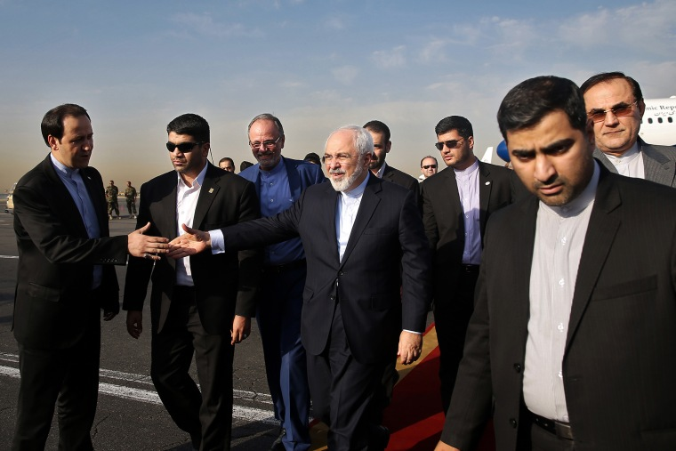 Iran's Foreign Minister Mohammad Javad Zarif, who is also Iran's top nuclear negotiator, center, shakes hands with an official upon arrival at the Mehrabad airport in Tehran, Iran, July 15, 2015. (Photo by Ebrahim Noroozi/AP)