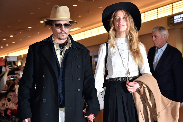 Actor Johnny Depp (L), accompanied by his fiancee US actress and model Amber Heard (R), arrive at Tokyo International Airport on Jan. 26, 2015. (Photo by Yoshikazu Tsuno/AFP/Getty)