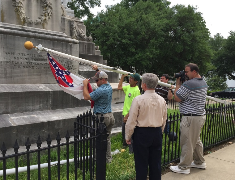 State workers take down a Confederate national flag on the grounds of the state Capitol, June 24, 2015, in Montgomery, Ala. Alabama Gov. Robert Bentley ordered Confederate flags taken down from a monument at the state Capitol.