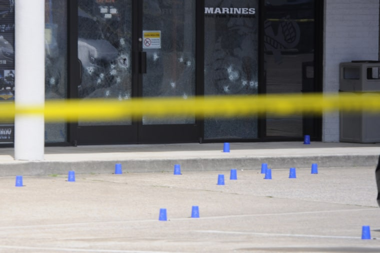 The windows of the Armed Forces Recruitment Center have several bullet holes from a shooting as the area is cordoned off with blue shell casing markers in the parking lot, July 16, 2015 in Chattanooga, Tenn. (Tim Barber/Chattanooga Times Free Press/AP)