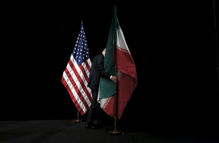 A staff removes the Iranian flag from the stage after a group picture with foreign ministers and representatives during the Iran nuclear talks at the Vienna International Center in Vienna