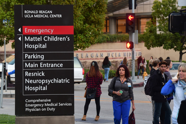 Pedestrians and students watch media gathered outside the Ronald Reagan UCLA Medical Center in Los Angeles, Calif. on March 5, 2015. (Photo by Frederic J. Brown/AFP/Getty)