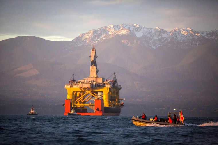 A small boat crosses in front of an oil drilling rig as it arrives in Port Angeles, Wash. on April 17, 2015. (Photo by Daniella Beccaria/seattlepi.com/File/AP)