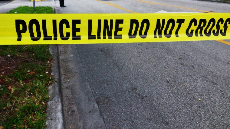 Police tape blocks the street to an apartment building after a shooting incident which began Friday evening left seven people dead in Hialeah