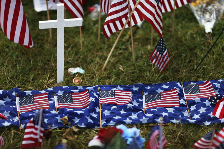 Five American flags in honor of the five killed are seen lain out in the memorial near the Armed Forces Career Center/National Guard Recruitment Office which had been shot up on July 19, 2015 in Chattanooga, Tenn. (Photo by Joe Raedle/Getty)
