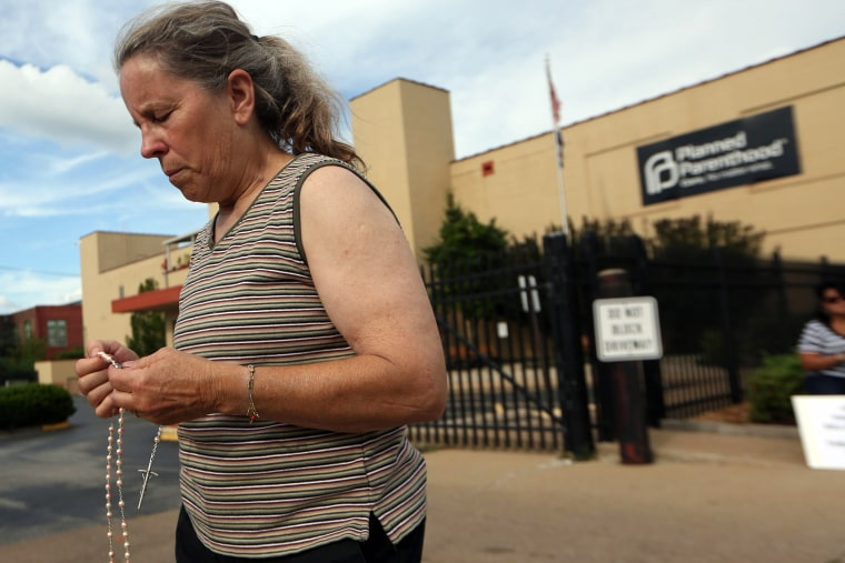Mary Roy, of Potosi, Mo., holds a rosary in support of a pro-life rally, July 21, 2015, outside a Planned Parenthood building in St. Louis.
