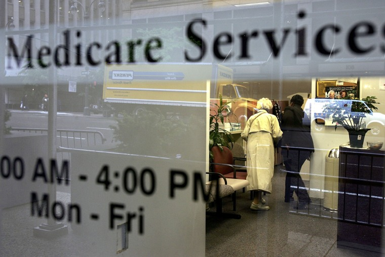Two people walk inside a Medicare Services office. (Photo by Spencer Platt/Getty)