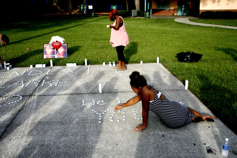 Lashell Bell, 18, right, of Tampa places candles spelling out ''We Love You'' during a vigil on July 22, 2015 in Florida, in memory of India Clarke. (Photo by Octavio Jones/Tampa Bay Times/Zuma)