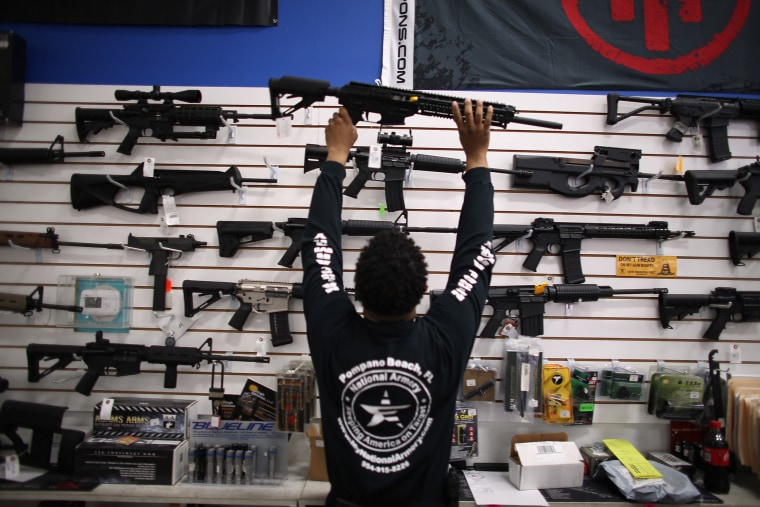 A man puts a weapon on display (Photo by Joe Raedle/Getty).