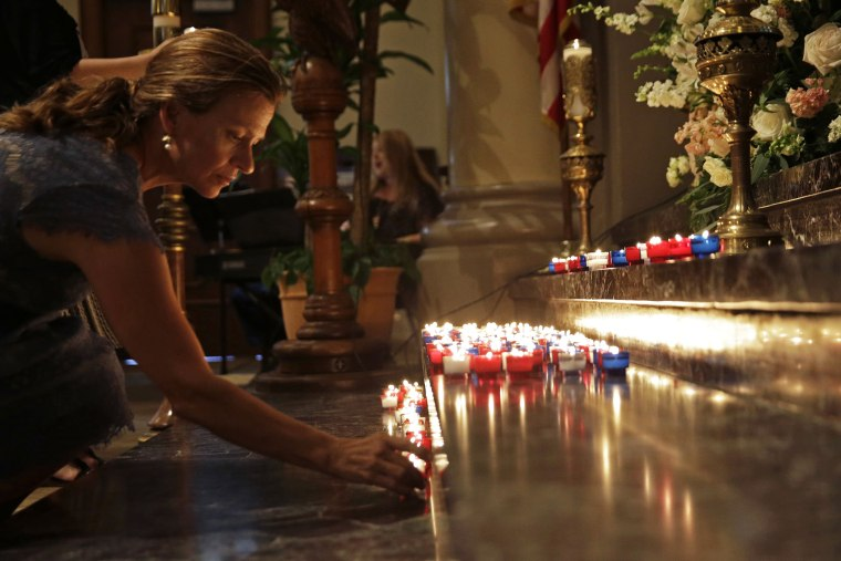 A woman places a candle on the altar during a prayer service for the victims of The Grand 16 theater shooting at the Cathedral of St. John the Evangelist, in Lafayette, La., July 26, 2015. (Photo by Gerald Herbert/AP)