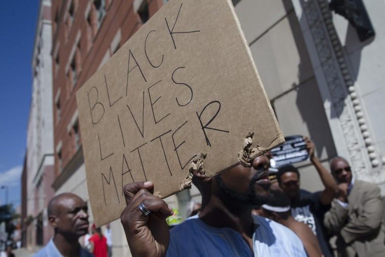Demonstrators hold signs outside the office of Hamilton County prosecutor Joe Deters' office during a protest demanding release of video showing the shooting death of Samuel Dubose on July 23, 2015, in Cincinnatti, Ohio. (Photo by John Minchillo/AP)