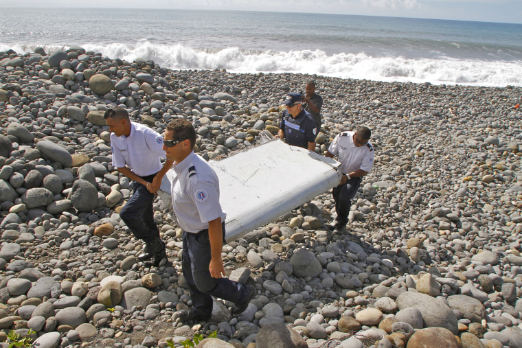French police officers carry a piece of debris from a plane in Saint-Andre, Reunion Island (Photo by Lucas Marie/AP).