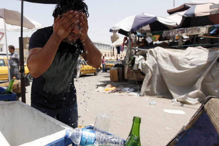 A man washes his face to cool off during a warm summer day in Baghdad (Photo by Ahmed Saad/Reuters).