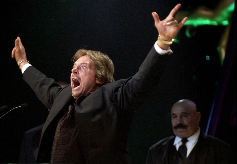 Wrestler Rowdy Roddy Piper gestures to the crowd as wrestler The Iron Sheik looks on after being inducted into the WWE Hall of Fame at the Induction Ceremony in Universal City, Calif., April 2, 2005. (Photo by Matt Sayles/AP)