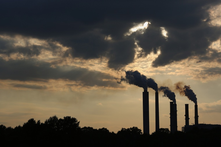 The silhouettes of emissions are seen rising from stacks of the Duke Energy Corp. Gibson Station power plant at dusk in Indiana, July 23, 2015. (Photo by Luke Sharrett/Bloomberg/Getty)