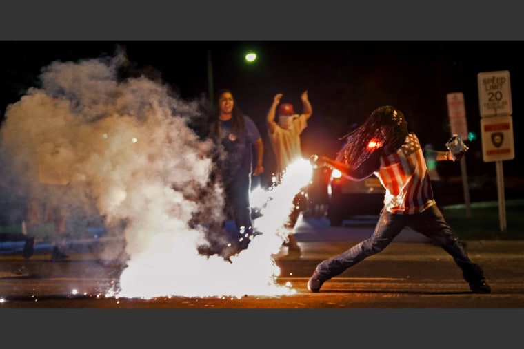 Edward Crawford returns a tear gas canister fired by police who were trying to disperse protesters in Ferguson, Mo., Aug. 13, 2014.