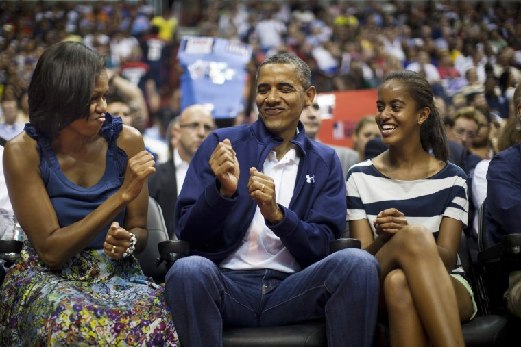 US President Barack Obama does a little dance while First Lady Michelle Obama and Malia Obama look on in Washington DC on July 16, 2012. (Photo by Jim Lo Scalzo/EPA)