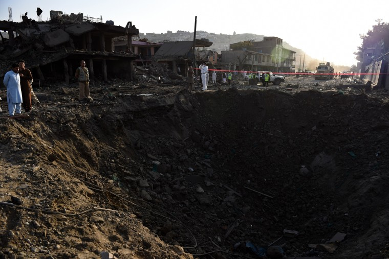 Afghan security forces and residents stand near the crater from a powerful truck bomb in Kabul on Aug. 7, 2015. (Photo by Wakil Kohsar/AFP/Getty)