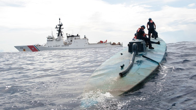 In this July 19, 2015 photo released by the U.S. Coast Guard, a Coast Guard Cutter Stratton boarding team investigates a self-propelled semi-submersible. (Photo by LaNola Stone/U.S. Coast Guard/ AP)