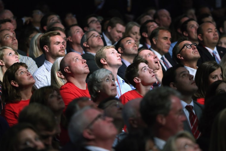 Audience members look up at the large video screen hanging above the first prime-time Republican presidential debate hosted by FOX News and Facebook at the Quicken Loans Arena on Aug. 6, 2015 in Cleveland, Ohio. (Photo by Chip Somodevilla/Getty)