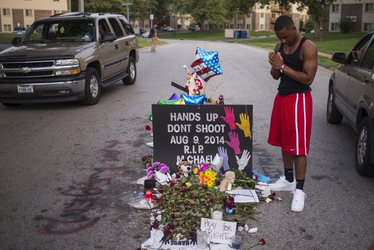 Local resident Ken Kendricks Jr. puts his hands together in prayer at a makeshift memorial at the site along Canfield Road where unarmed teen Michael Brown was shot dead in Ferguson, Mo., Aug. 22, 2014. (Photo by Adrees Latif/Reuters)