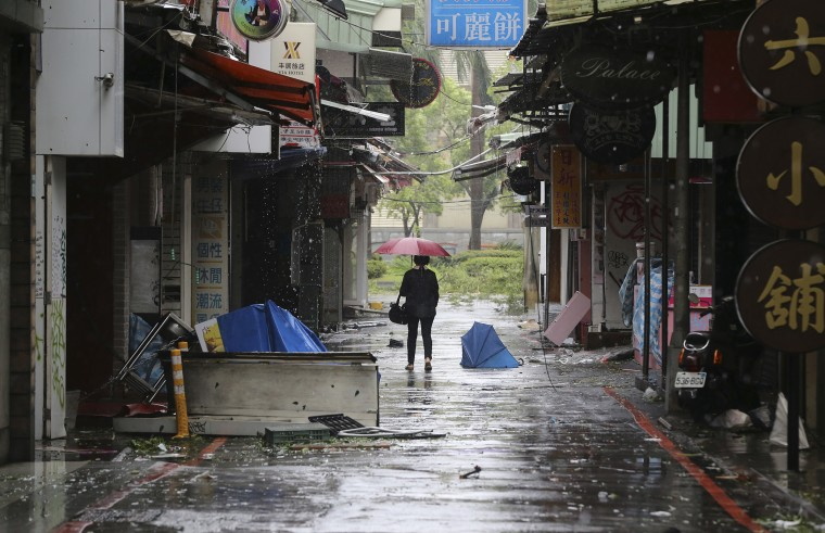 A woman walks down a back alley filled with debris from Typhoon Soudelor in Taipei, Taiwan, Aug. 8, 2015, after Soudelor brought heavy rains and strong winds to the island. (Photo by Wally Santana/AP)