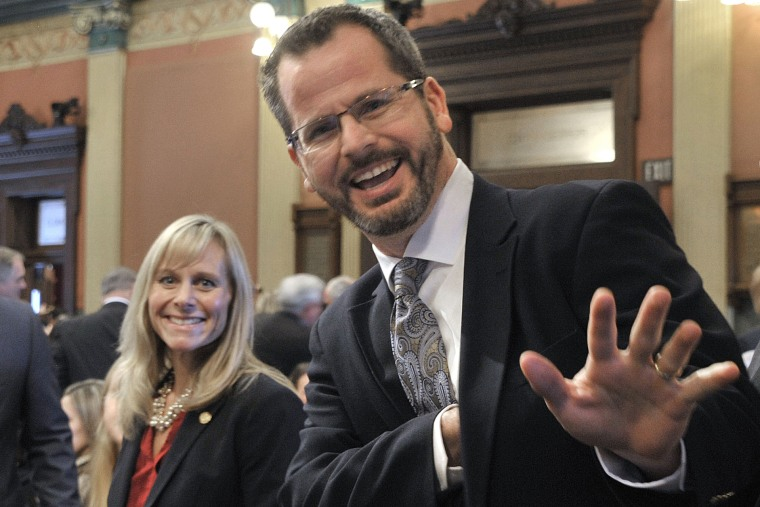 In this Jan. 14, 2015 photo, Rep. Cindy Gamrat, R-Plainwell, and Rep Todd Courser, R-Lapeer wave to reporters in the House of Representatives in Lansing. (Photo by Dale G. Young/Detroit News/AP)
