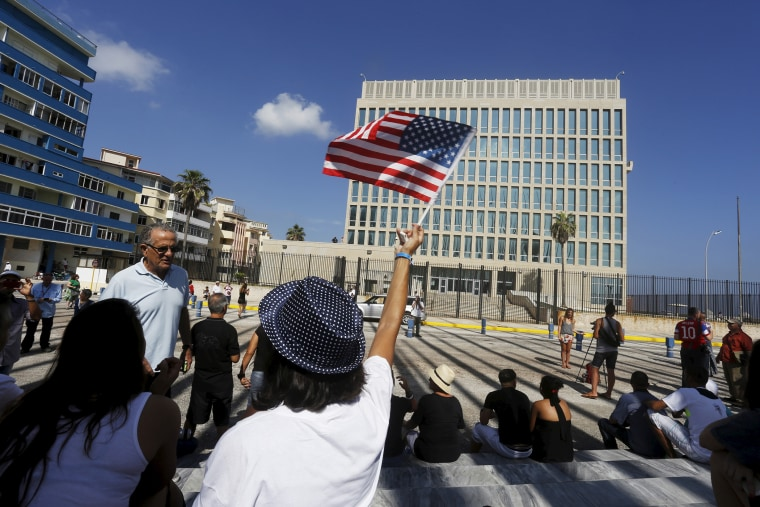 A woman waves a U.S flag in front of the U.S. Interests Section, in Havana, Cuba. (Photo by  Stringer/ Reuters)