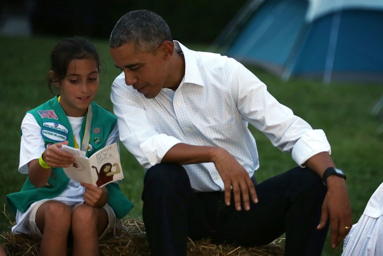 Daphnye Shell reads a book with U.S. President Barack Obama during a campfire songs session at the first-ever White House Campout (Photo by Alex Wong/Getty).