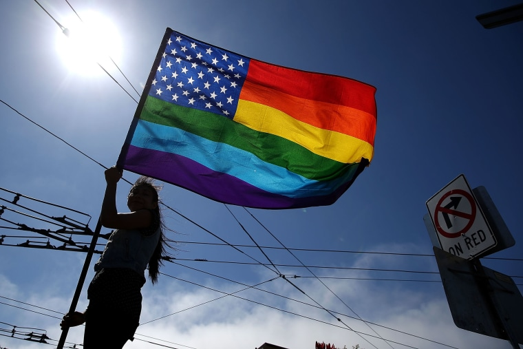 A same-sex marriage supporter waves a pride flag (Photo by Justin Sullivan/Getty).
