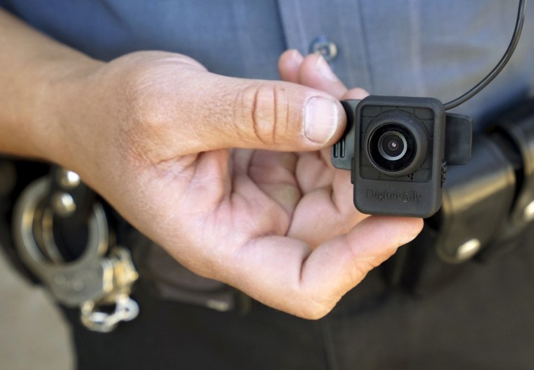 A Colorado Springs police officer poses with a Digital Ally First Vu HD body worn camera outside the police department in Colorado Springs April 21, 2015. (Photo by Rick Wilking/Reuters)